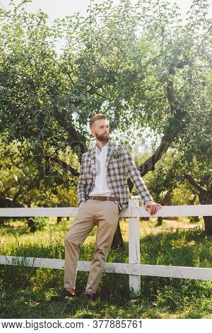 Handsome Bearded Man In Vintage Clothing. Portrait Stylish Groom In Plaid Jacket On His Wedding Day