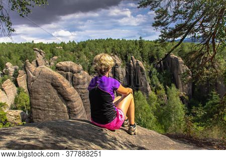 Female Active Traveler Sitting On The Rock. Girl Enjoying The Views From A Peak In The Mountains. Br