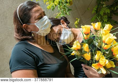 Women Mourning Those Lost To The Coronavirus, Wearing Face Masks, Showing Mutual Support, Hugging