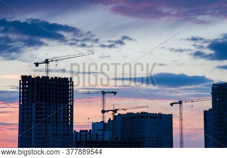 Tower Cranes In Action At Construction Site On Sunset Background. Crane The Build The High-rise Buil