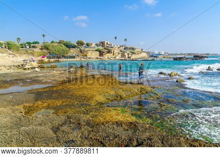 Achziv, Israel - July 22, 2020: View Of Visitors Fishing And Bathing, Bay, Coast, And Old Buildings,