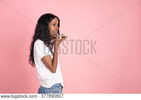 Recording Voice. Cheerful African-american Young Woman Isolated On Pink Background, Emotional And Ex