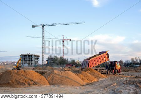 Dump Truck Unloading Earth Sand For Road Construction Or For Foundation Work. Work Of Tower Crane At