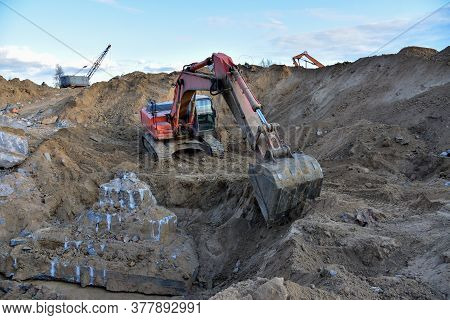 Excavator Digg Ground In Open Pit At Landfill For Work Concrete Demolition Waste. Salvaging And Recy