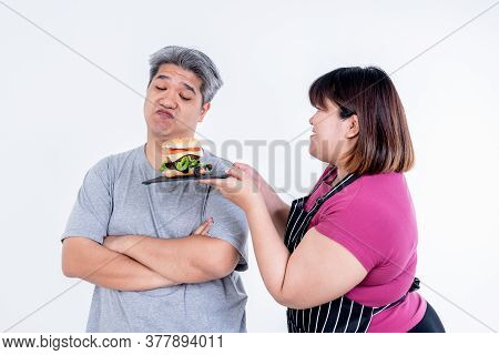Portrait Images Of Asian Wife Obese Persuading Her Husband To Eat A Hamburger That She Prepared On W