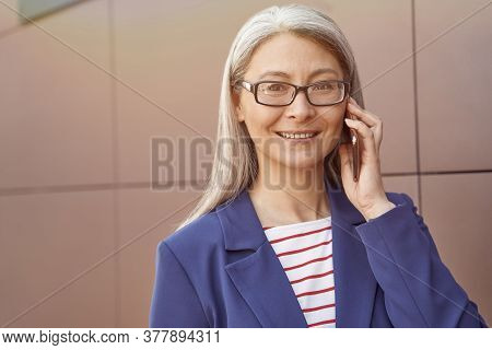 Good Business Talk. Portrait Of A Happy Mature Business Woman Wearing Eyeglasses And Classic Wear Ta