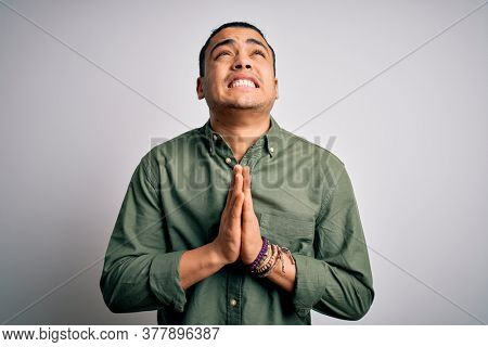 Young brazilian man wearing casual shirt standing over isolated white background begging and praying with hands together with hope expression on face very emotional and worried. Begging.
