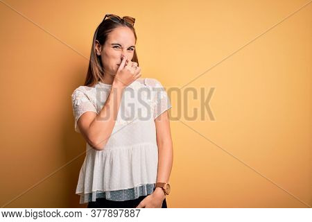 Young beautiful woman wearing casual t-shirt and sunglasses over isolated yellow background smelling something stinky and disgusting, intolerable smell, holding breath with fingers on nose. Bad smell