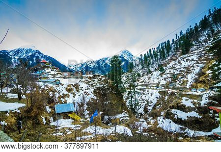 A Landscape Of A Snow Capped Valley With Trees And Houses. Mountain With Snow Capped Peaks And Blue