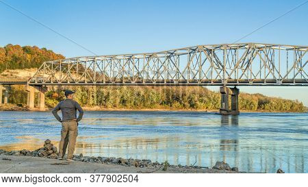 Lonely male figure at the old boat ramp on Missouri River at Taylor's Landing near Rocheport, MO, fall colors scenery with the bridge view