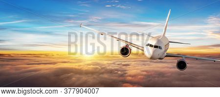 Commercial airplane flying above clouds, beautiful sunset ligt, panoramic view.
