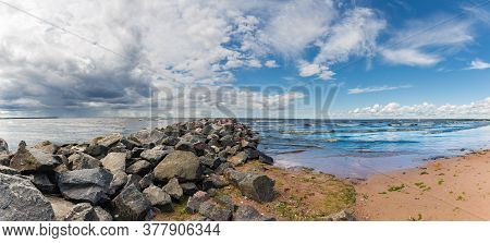 Panorama With A Stone Breakwater Going Into The Sea. The Contrast Of A Rainy Sky On The Left And A C