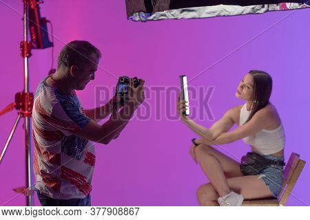 Photographer Takes Pictures Of Young Woman Holding New Led Lamp While Posing On Purple Background. P
