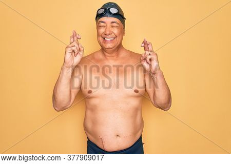 Middle age senior grey-haired swimmer man wearing swimsuit, cap and goggles gesturing finger crossed smiling with hope and eyes closed. Luck and superstitious concept.