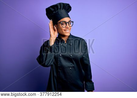 Young african american chef girl wearing cooker uniform and hat over purple background smiling with hand over ear listening an hearing to rumor or gossip. Deafness concept.