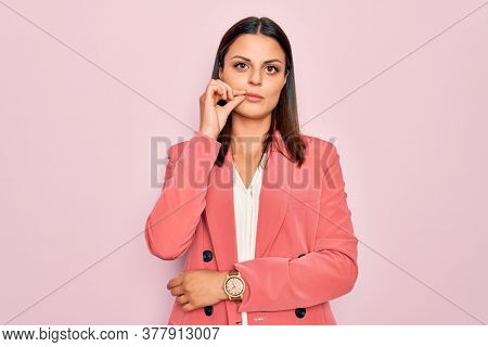 Young beautiful brunette businesswoman wearing elegant jacket over isolated pink background mouth and lips shut as zip with fingers. Secret and silent, taboo talking