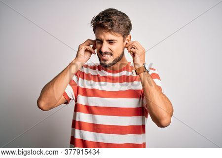 Young handsome man with beard wearing striped t-shirt standing over white background covering ears with fingers with annoyed expression for the noise of loud music. Deaf concept.