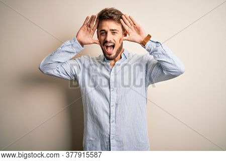 Young handsome man with beard wearing striped shirt standing over white background Smiling cheerful playing peek a boo with hands showing face. Surprised and exited
