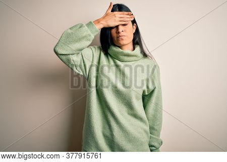Young beautiful hispanic woman wearing green winter sweater over isolated background covering eyes with hand, looking serious and sad. Sightless, hiding and rejection concept
