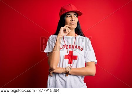 Young beautiful hispanic lifeguard woman wearing safeguard t-shirt and whistle with hand on chin thinking about question, pensive expression. Smiling with thoughtful face. Doubt concept.