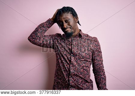 Young handsome african american man wearing casual shirt standing over pink background confuse and wondering about question. Uncertain with doubt, thinking with hand on head. Pensive concept.