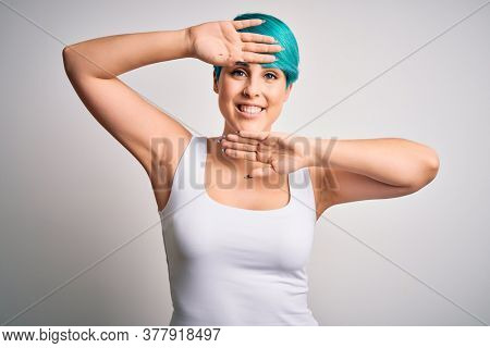 Young beautiful woman with blue fashion hair wearing casual t-shirt over white background Smiling cheerful playing peek a boo with hands showing face. Surprised and exited