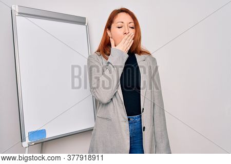 Young beautiful redhead businesswoman doing business presentation using magnetic board bored yawning tired covering mouth with hand. Restless and sleepiness.
