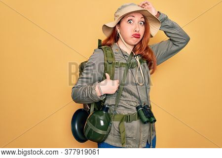 Young redhead backpacker woman hiking wearing backpack and hat over yellow background worried and stressed about a problem with hand on forehead, nervous and anxious for crisis