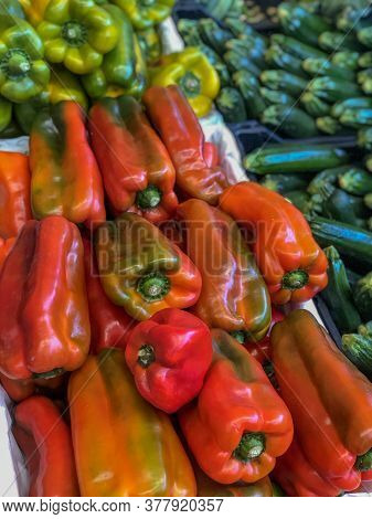 Fresh Red And Yellow Peppers On The Market Close-up Across Other Vegetables. Organic Food. Salad Ing