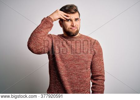 Young blond man with beard and blue eyes wearing casual sweater over white background worried and stressed about a problem with hand on forehead, nervous and anxious for crisis