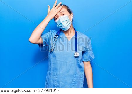 Young blonde woman wearing doctor uniform and medical mask surprised with hand on head for mistake, remember error. forgot, bad memory concept.