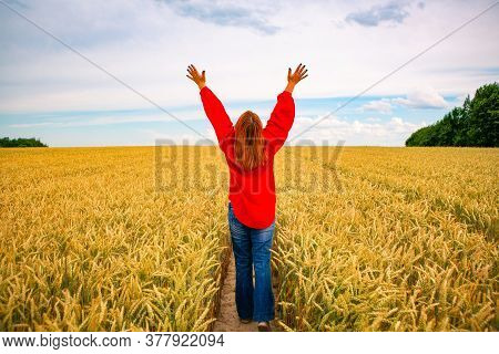 Woman With Outstretched Arms In A Wheat Field, Bright Summer Background