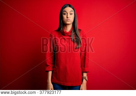 Young beautiful brunette woman wearing casual sweater over isolated red background puffing cheeks with funny face. Mouth inflated with air, crazy expression.