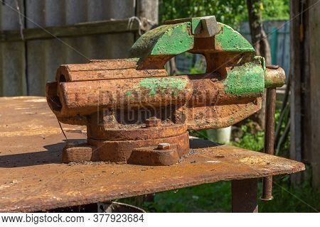 Old Rusty Steel Clamp Vise Iron Metal Tool In The Workshop Workbench In Day Side View