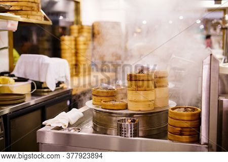 Chinese cuisine dim sum been cooked in steamer baskets at traditional restaurant