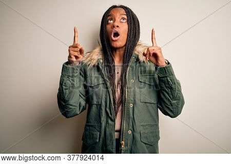 Young african american woman wearing winter parka coat over isolated background amazed and surprised looking up and pointing with fingers and raised arms.