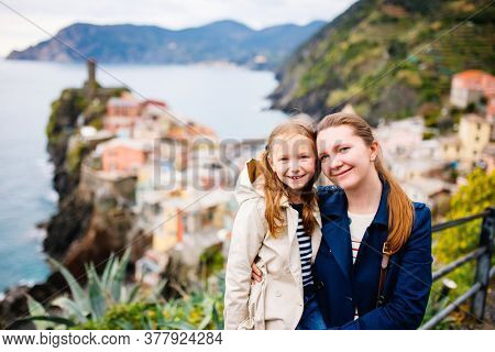Mother and daughter enjoying scenic view of colorful Vernazza village in Cinque Terre Italy