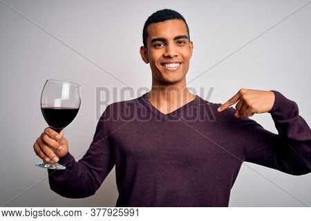 Handsome african american sommelier man tasting glass of red wine over white background with surprise face pointing finger to himself