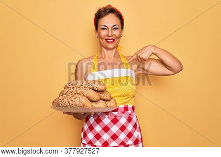 Middle age senior housewife pin up woman wearing 50s style retro dress cooking wholemeal bread with surprise face pointing finger to himself