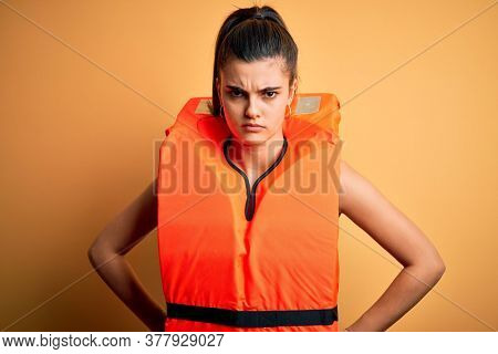 Young beautiful brunette woman wearing orange safe lifejacket over yellow background skeptic and nervous, disapproving expression on face with crossed arms. Negative person.