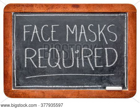 face masks required  - white chalk handwriting on a slate blackboard, business sign during the coronavirus covid-19 pandemic and social distancing