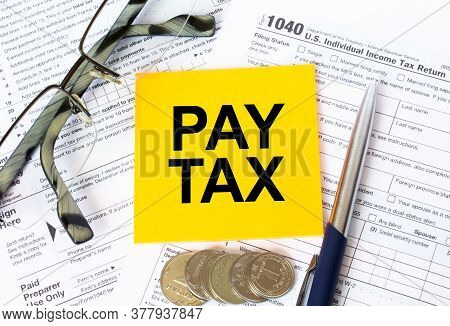 Tax-filling Concept. Text Pay Tax On Note Paper With The U.s Irs 1040 Form,pen And Glasses