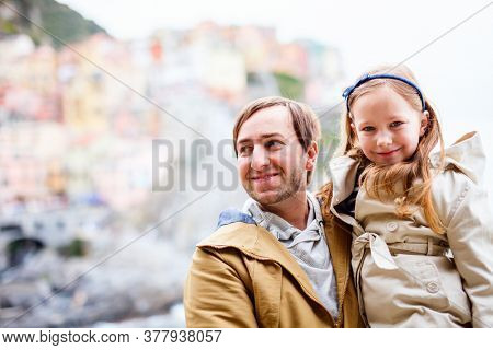 Father and daughter enjoying scenic view of colorful Vernazza village in Cinque Terre Italy