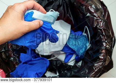 Hand Throwing Out Discarded Medical Gloves And Protective Masks In The Trash Bin After Quarantine
