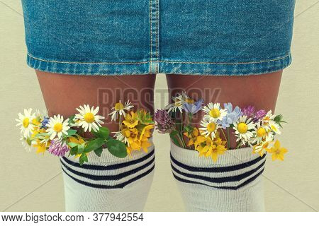 Female Legs With Fresh Flowers In Stockings. A Young Hipster Girl With Flowers From White Stockings