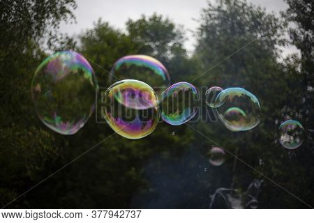 A Large Soap Bubble Flies Through The Air. The Bubble Shimmers With All Colors.