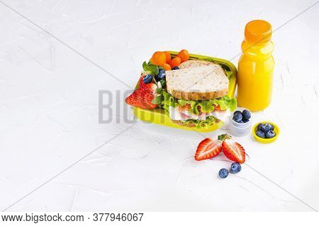 Box With School Lunch And A Bottle Of Juice. Sandwich With Cheese And Salad, Fresh Berries For Baby