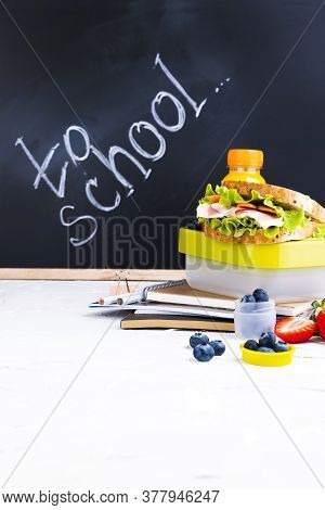 Box With School Lunch Near The Black Board. Healthy Food For A Child. Toast With Salad And Strawberr