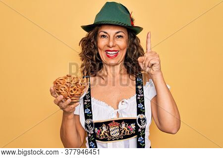 Middle age woman wearing traditional octoberfest dress holding bowl with baked pretzels surprised with an idea or question pointing finger with happy face, number one