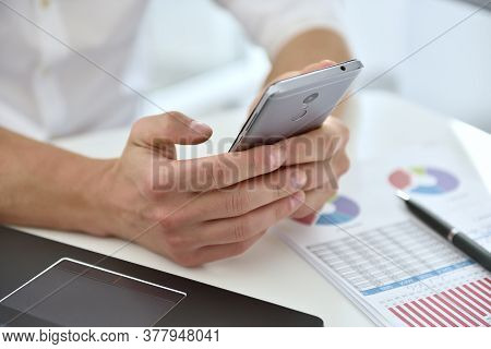 Businessman With Mobile Phone Analyzing At Graph And Checking Business Plan. Investment And Financia